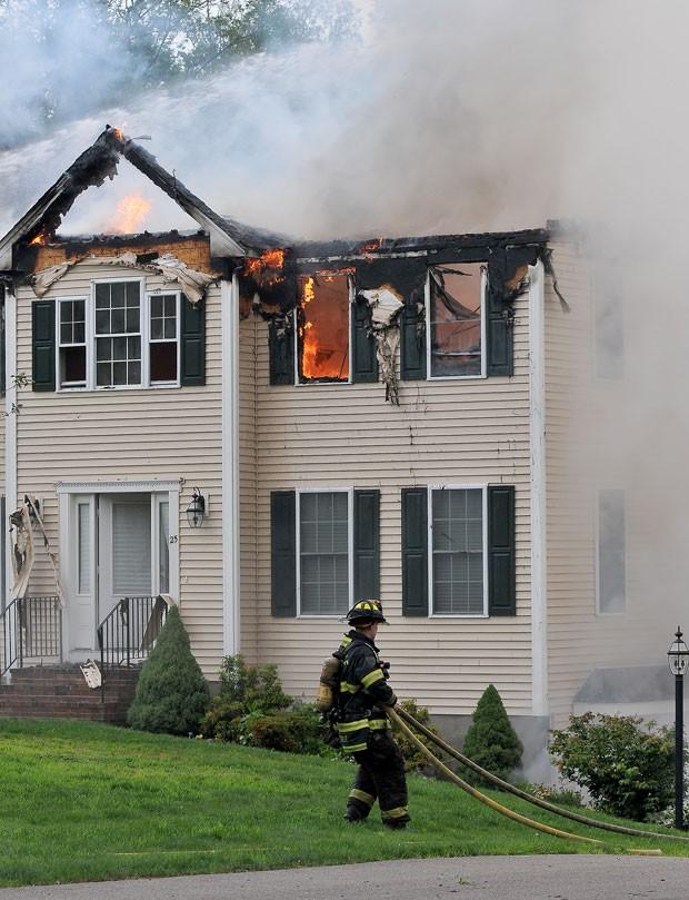 Três pessoas morreram na queda de um pequeno avião sobre uma casa no estado de Massachusetts, nordeste dos Estados Unidos, mas os moradores da residência conseguiram escapar do grande incêndio provocado pelo acidente (Foto: Mark Stockwell/The Sun Chronicle via AP)