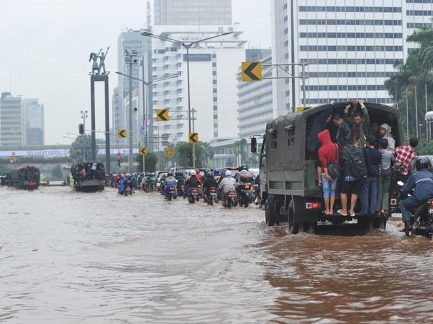 População usa caminhões militares para chegar aos seus escritórios em uma rua inundada principal em Jacarta  (Foto: AFP PHOTO / ADEK BERRY)