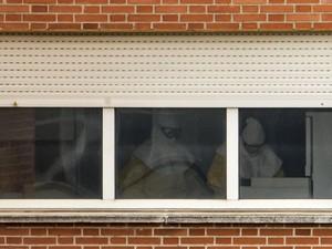 Profissionais da saúde usando roupa protetora trabalham em ala de isolamento do Hospital Carlos III, onde Teresa está internada  (Foto: AFP photo/Pedro Armestre)