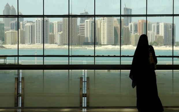 Mulher olha para prédios de Abu Dhabi, nos Emirados Árabes Unidos (Foto: Flávia Mantovani/G1)
