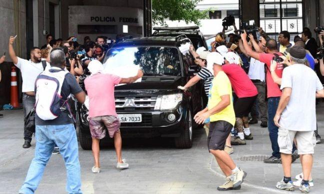 Manifestantes festejam, com guardanapos na cabeça, a saída de Cabral da Pilícia Federal (Foto: Tasso Marcelo / AFP)