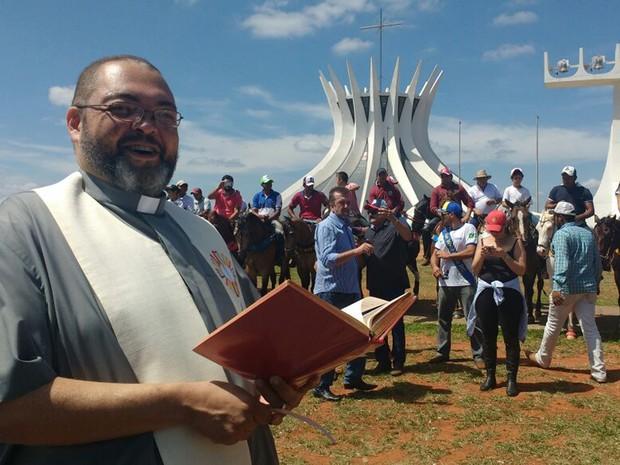O padre João Firmino, da Catedral de Brasília, fazia oração ao lado dos vaqueiros (Foto: Elielton Lopes/G1)