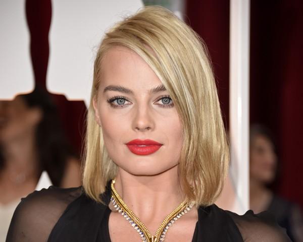 Margot Robbie com a risca dividiva bem na leteral e o cabelo escondido atrás da orelha (Foto: Getty Images)