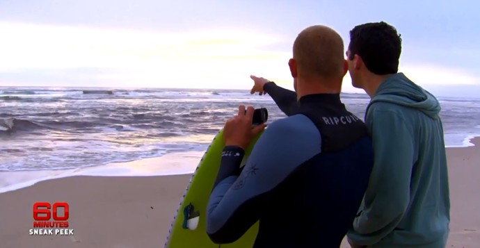 Mick Fanning aponta o dedo para o mar e mostra onde está o tubarão que o fez sair do mar (Foto: Reprodução/Youtube/60minutes)