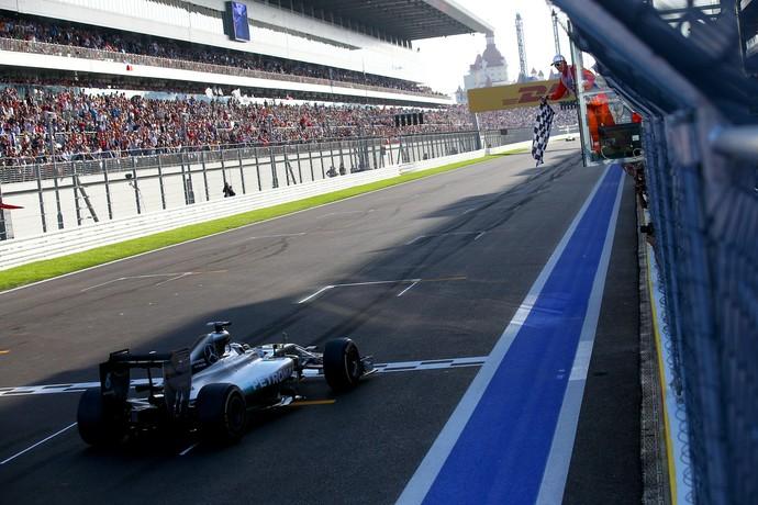 Diante de arquibancadas lotadas, Lewis Hamilton recebe a bandeirada para a vitória do primeiro GP da Rússia (Foto: Getty Images)