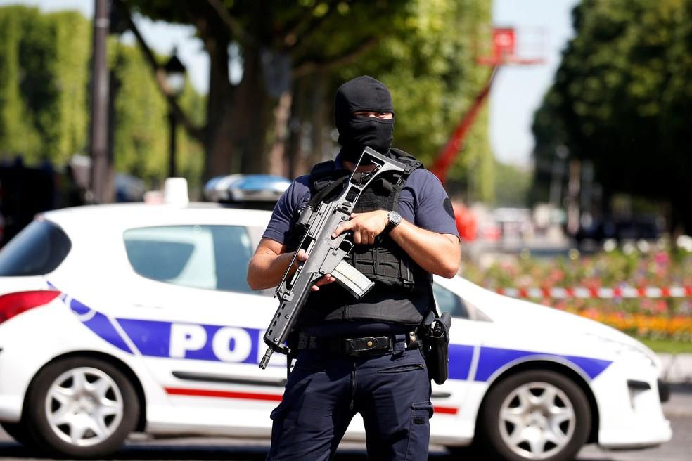 Policial faz segurança na Champs Élysées, em Paris, nesta segunda-feira (19),  após carro bater em van da polícia (Foto:  Gonzalo Fuentes/ Reuters)