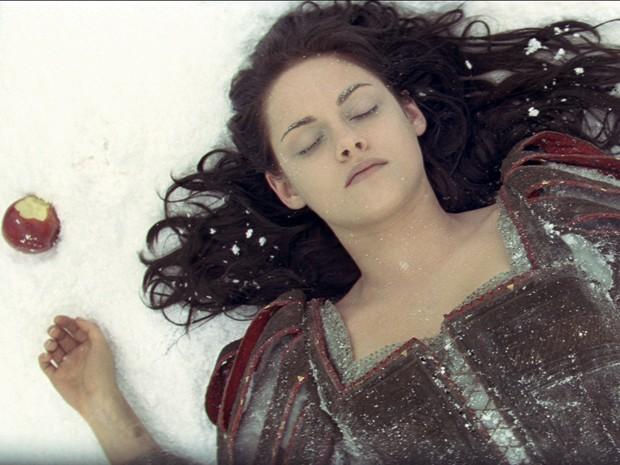 Branca de Neve (Kristen) desmaiada após morder a maça envenenada pela rainha Ravenna (Foto: Divulgação)