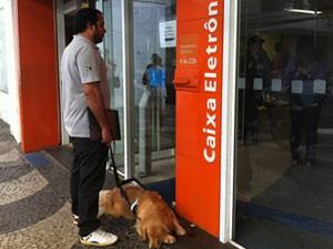 O instrutor George Thomaz Harrison e o cão-guia não conseguem entrar em agência bancária de Niterói (Foto: Carolina Lauriano/G1)