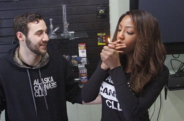 Peter Lomonaco, co-fundador do Alaska Cannabis Club, acende cigarro de maconha de Charlo Greene, CEO do clube, em foto de 20 de fevereiro (Foto: Mark Thiessen/AP)