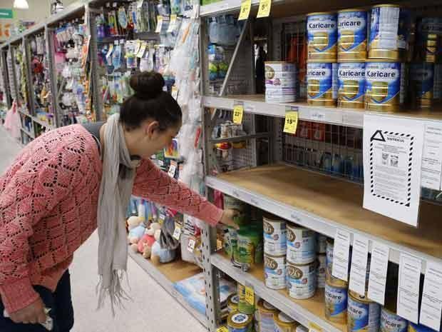 Consumidora escolhe leite em pó na cidade de Huntly, na Nova Zelândia: comunicado na prateleira avisa que alguns lotes de um produto da Danone foram banidos. (Foto: Reuters/Nigel Marple)