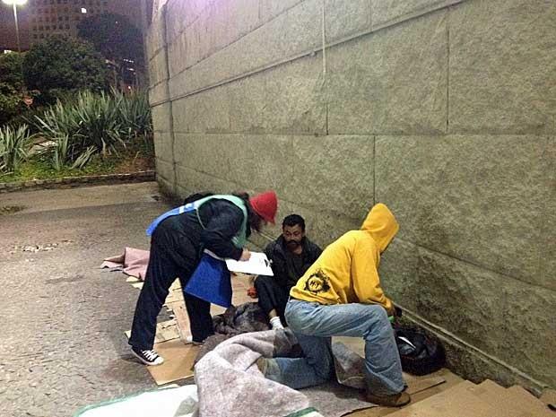 Assistente social tenta convencer moradores de rua a irem para abrigo da Prefeitura na noite de terça-feira (23). (Foto: Helton Simões Gomes / G1)
