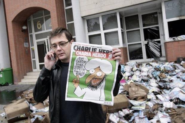 Editor da Charlie Hebdo mostra desenho polêmico em ataque em 2011 (Foto: Alexander Klein/AFP)
