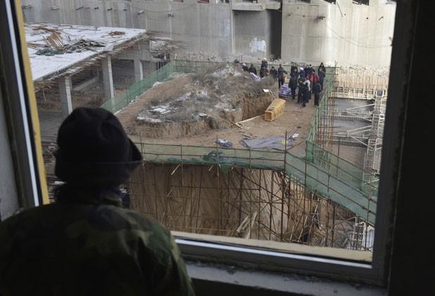 Operário observa retirada de túmulo que ficava em meio a prédio em construção (Foto: Reuters)