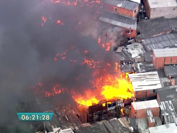 Às 6h30, bombeiros trabalhavam para evitar que fogo se alastrasse em favela de Sapopemba, na Zona Leste de São Paulo, na manhã desta sexta (23) (Foto: Reprodução/TV Globo)