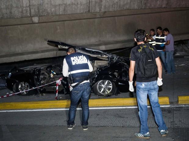Policiais olham carro destruído por queda de ponte em Guayalquil, no Equador, no sábado (16) (Foto: Jeff Castro/AP)
