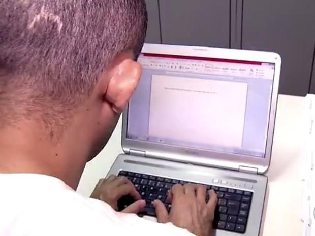 Nilton digitaliza páginas manuscritas; notebook foi presente de juiz (Foto: Reprodução/ Inter TV Cabugi)