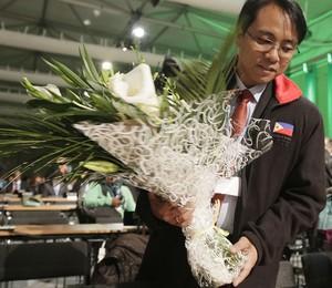 Yeb Sano, negociador climático das Filipinas, recebe flores em homenagem às vítimas do tufão Haiyan. Ele participa de conferência do clima em Varsóvia, Polônia, a COP-19 (Foto: Czarek Sokolowski/AP)