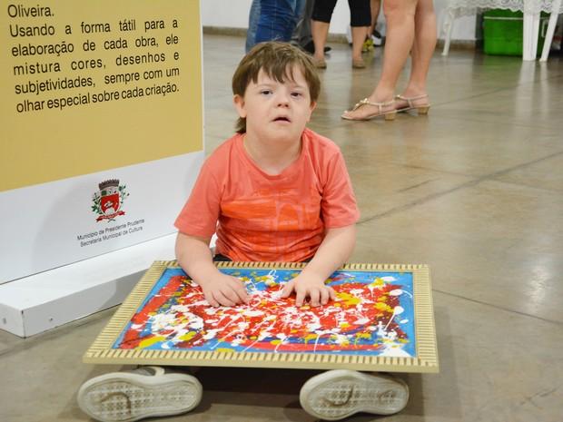 Matheus Fernandes Raimundo, de 9 anos, faz pinturas com as mãos (Foto: Olímpio Moura/Divulgação)