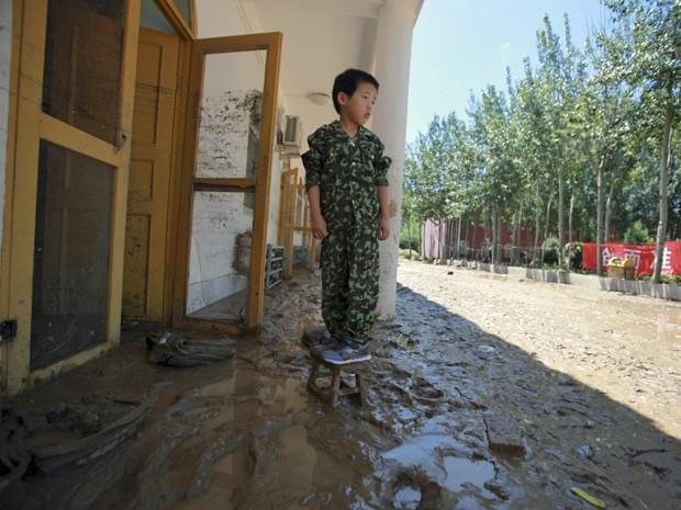 Um estudante de escola primária olha para os seus pertences na lama após a inundação no distrito de Fangshan (Foto: Stringer/Reuters)