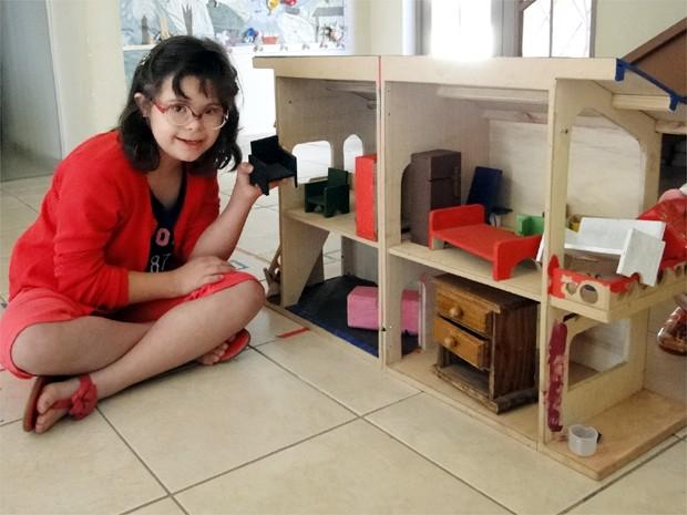 Ana Luisa está pintando a casinha de bonecas que ganhou no Natal (Foto: Adriano Oliveira/G1)