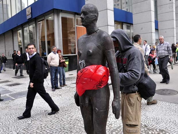 Homem tenta cobrir nudez de est&#225;tua com sacola pl&#225;stica no Centro de SP (Foto: Cris Faga/AE)