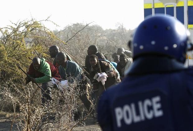 Policial atira em mineiros durante confronto nesta quinta-feira (16) na África do Sul (Foto: Reuters)