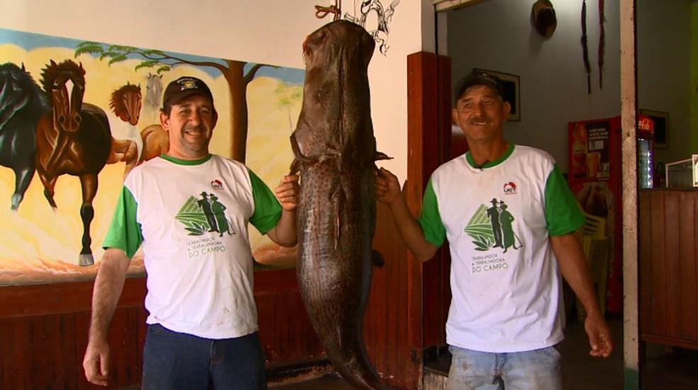 Alex e Castro posam ao lado do pintado de 60 quilos em Barretos, SP (Foto: Reprodução/EPTV)