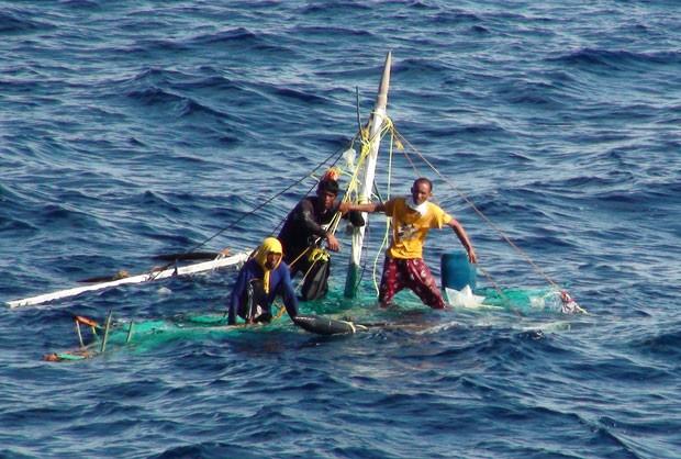 Trio de pescadores é avistado sobre a estrutura do pequeno barco, cinco dias após ele ser destruído por uma tempestade (Foto: AFP/Guarda Costeira de Taiwan)
