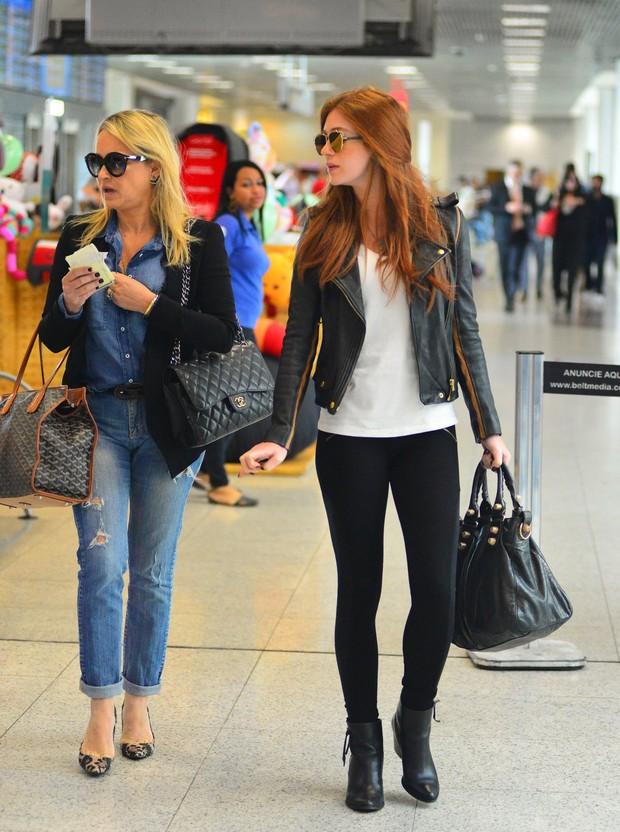 Atriz usando jaqueta de couro com calça leggin e bolsa estruturada preta, em shopping..