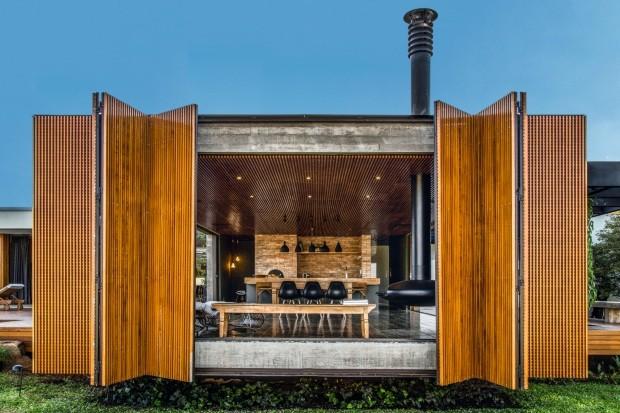 Desenhada pelo escritório mf+arquitetos, a porta com abertura tipo camarão é composta de painéis de muxarabi feitos de cedro. Ela ocupa todo o vão da fachada do bloco de concreto voltada para a floresta (Foto: Renato Moura / Divulgação)
