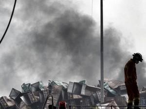Bombeiro caminha entre veículos danificados por explosões em Tianjin, China (Foto: Reuters/Stringer)