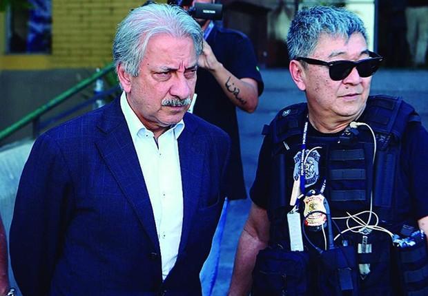 O empresário José Antunes Sobrinho, dono da Engevix, é escoltado após fazer exames de corpo de delito. Ele foi preso dentro da Operação Lava Jato (Foto: Geraldo Bubniak/AGB /Agência O Globo)