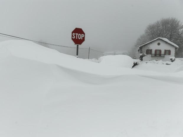 Um sinal de trânsito é quase encoberto pela neve na cidade de Burguete, nos Pirineus, na Espanha, na quinta (5) (Foto: AP Photo/Alvaro Barrientos)