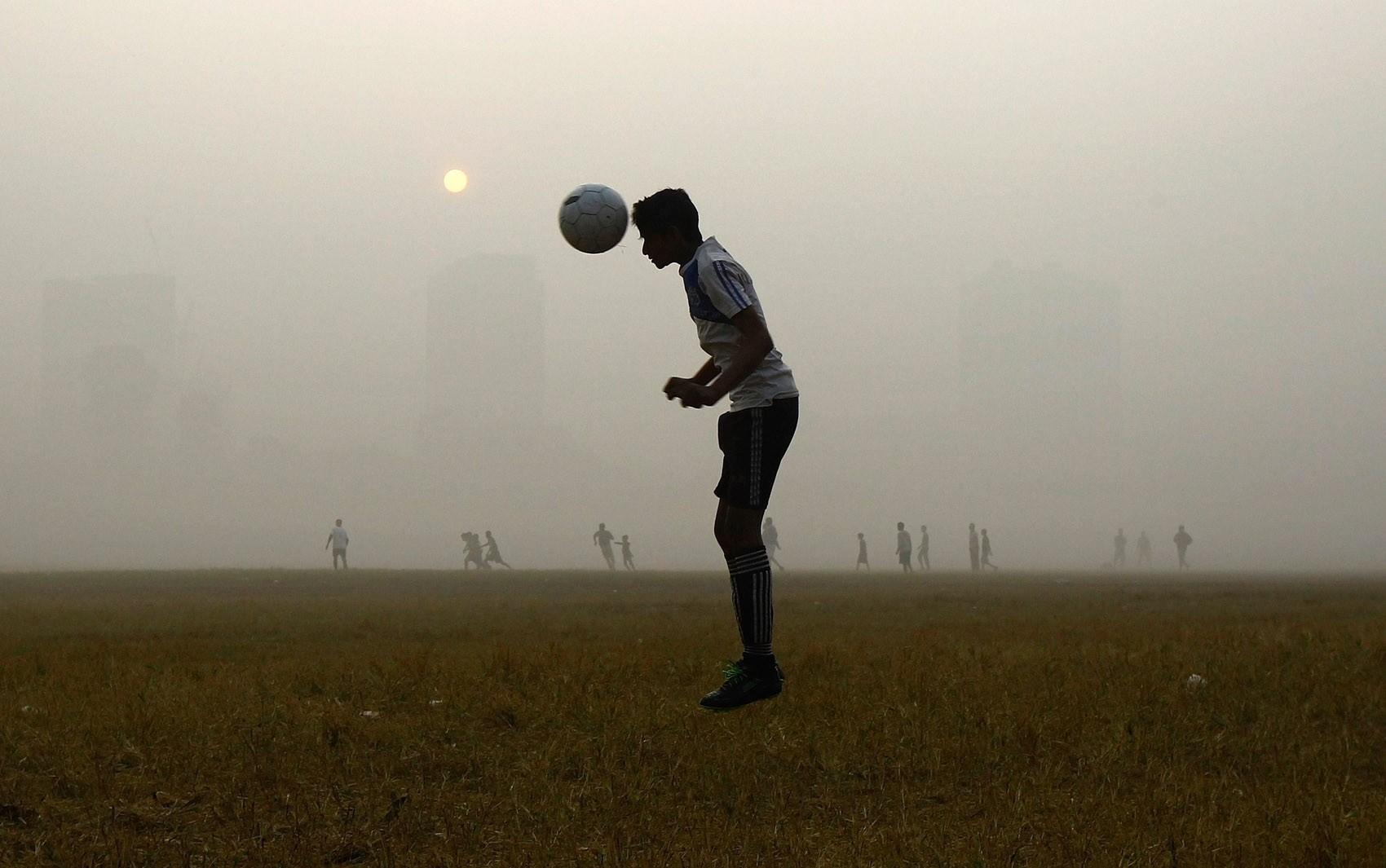 Um homem pula para cabecear durante treino de futebol em meio a neblina em um parque público de Kolkata, na Índia