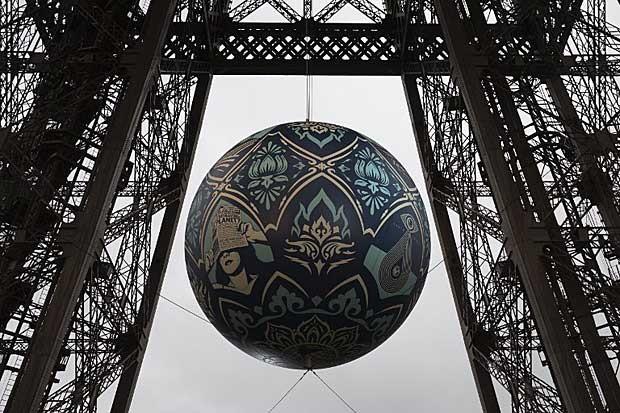 """Torre Eiffel recebe a esfera """"Crise Global"""" obra do artista plástico Shepard Fairey, para marcar a realização da cúpula do clima (Foto: Joel Saget/AFP)"""