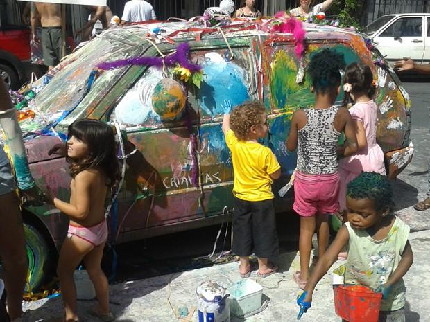 Crianças pintaram com tinta guache carro que estava na Praça Cairo, onde se concentrou o bloco Mama na Vaca. (Foto: Laura de Las Casas/G1)