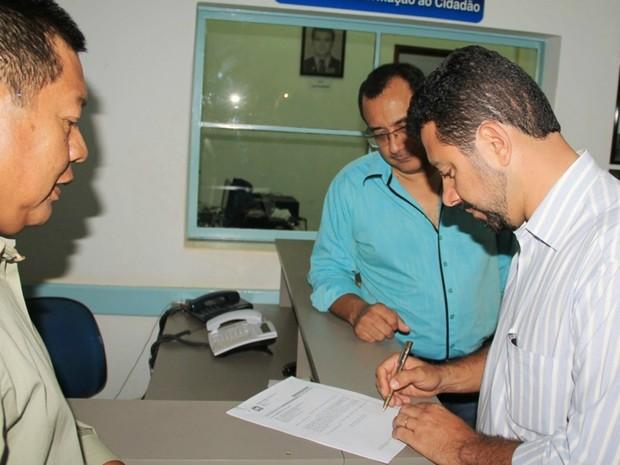 Wallas assinando a notificação na presença do oficial de Justiça (Foto: Asscom/Divulgação)