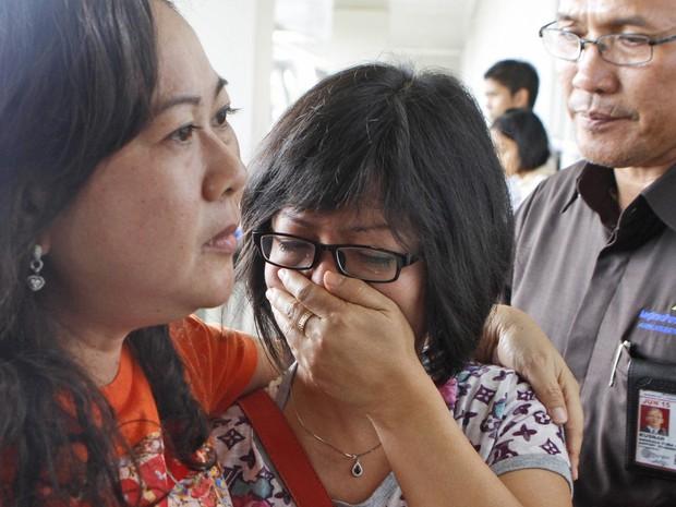 Mulher chora no centro de crise montado no Aeroporto Internacional Juanda, na Indonésia, enquanto aguarda notícias sobre o Airbus da AirAsia que desapareceu neste domingo (28) (Foto: Trisnadi/AP)
