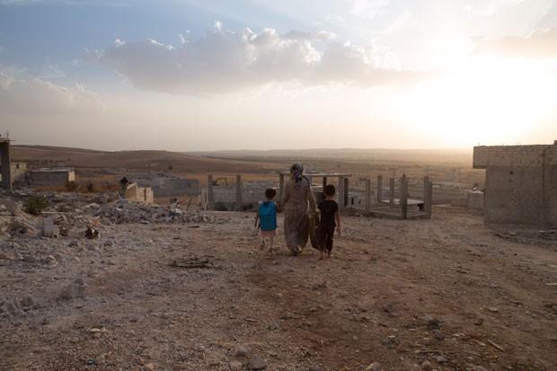Mulher e crianças em meios aos destroços na cidade síria de Kobane (Foto: Gabriel Chaim/G1)
