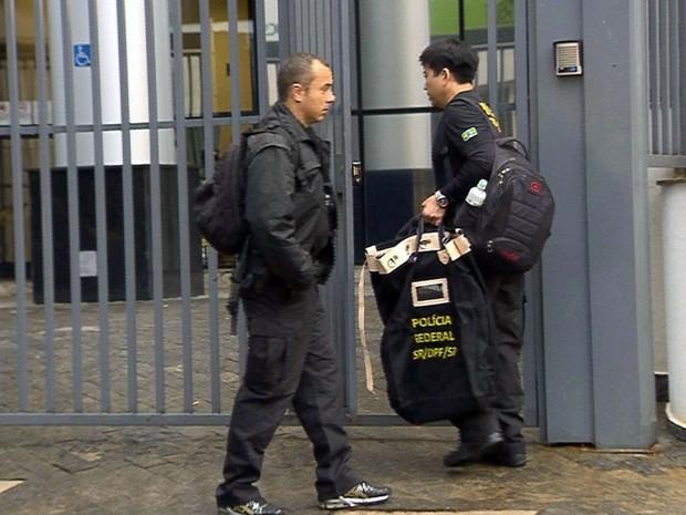 Policiais federais chegam com malotes na sede da instituição em Campinas (Foto: Reprodução EPTV)