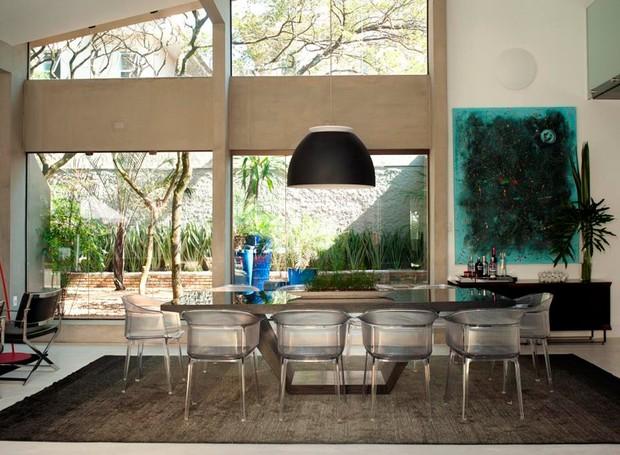 A sala de jantar, integrada ao living, tem mesa preta Calan da The Design Place. Cadeira papyrus acrílico cristal da Kartell. Arandela eclipse da Lumini (Foto: André Fortes/Divulgação)