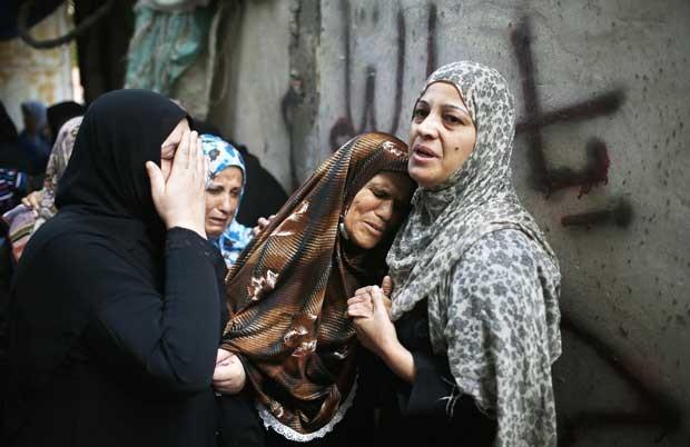 No centro, mãe de um dos palestinos mortos nesta quarta-feira (24) chora (Foto: Reuters)