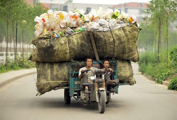 Homem leva um carona em triciclo carregado com pilha gigante de garrafas plásticas em uma rua de Taiyuan, na província chinesa de Shanxi (Foto: Reuters/Stringer)