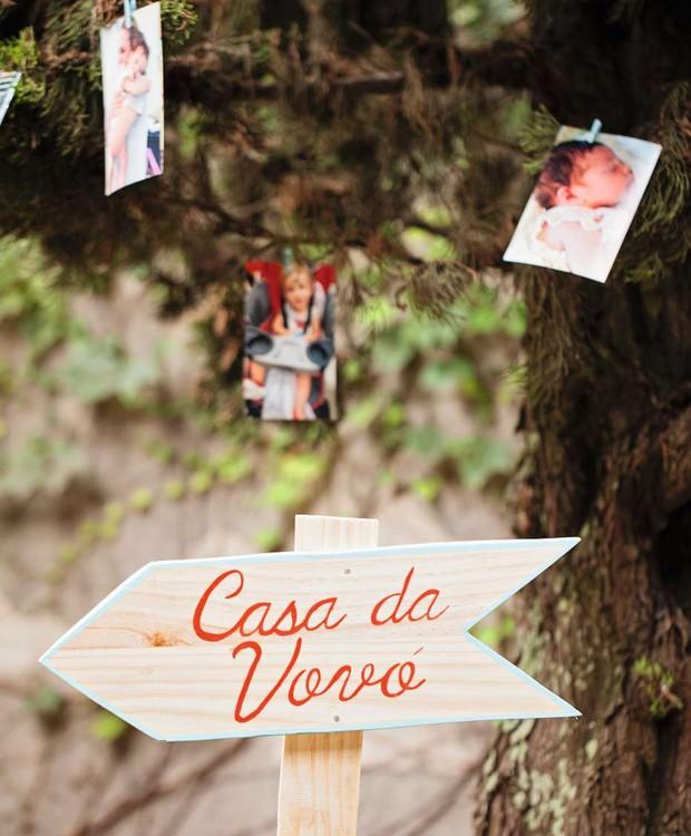 Fotos dos bebês em um varal improvisado e a dica para a casa da vovó no quintal. Placa Festa de Brincar (Foto: Elisa Correa)