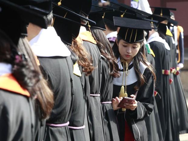 Formanda checa seu celular durante sua cerimônia de graduação na Universidade de Sungkyunkwan em Seul, na Coreia do Sul (Foto: Ahn Young-joon/AP)