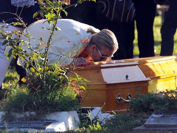 Livia Oliveira, mãe de Heitor, se ajoelha para beijar o caixão do filho durante enterro (Foto: Antonio Scorza/AFP)