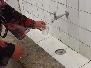 Turista pega água da Fonte da Bica, na Ilha de Itaparica. (Foto: Maiana Belo/G1 BA)