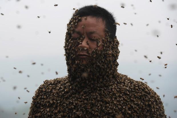 She Ping aparece coberto por abelhas em cidade na China (Foto: STR/AFP)