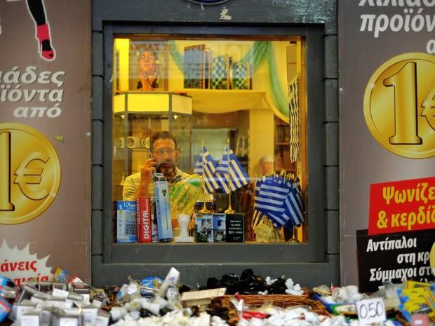 Em loja de itens para celulares vazia em Atenas, promoção anuncia 'vários produtos a partir de um euro' (Foto: Petros Karadjias / AP)