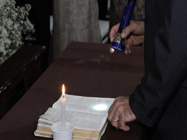 Pastor precisou de velas e lanternas para ler texto bíblico (Foto: Divulgação)